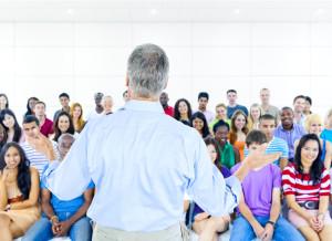 muž prednáša študentom, rozprávanie príbehov, skvelý rozprávač príbehov rozprávanie príbehov 27 techník pre charizmatickejšie rozprávanie príbehov (1. časť) bigstock Large group of Students in lec 64612057 300x218