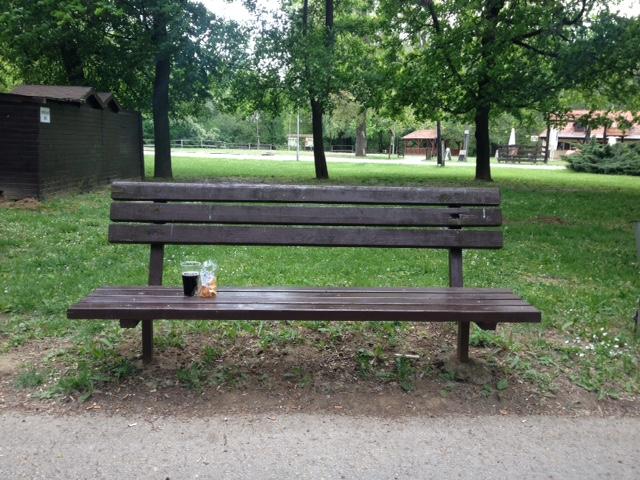 Lavička, na ktorej je kofola a balíček chrumiek  príťažlivosť Príťažlivosť: Prečo som sa rozhodol napísať vlastnú knihu? lavicka park nitra